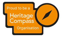 """Heritage Compass Organisation Badge. Yellow background with writing which reads """"Proud to be a Heritage Compass Organisation"""""""
